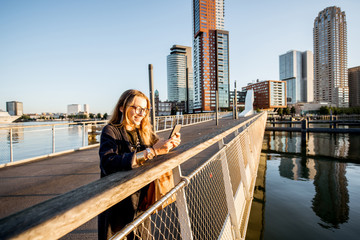 Woman standing with phone on the footbridge at the modern residential district during the morning in Rotterdam city
