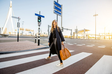 Fototapete - Stylish businesswoman crossing the street at the modern district during the morning in Rotterdam city