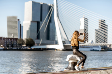 Fototapete - Woman enjoying beautiful cityscape view on the modern riverside during the morning in Rotterdam city