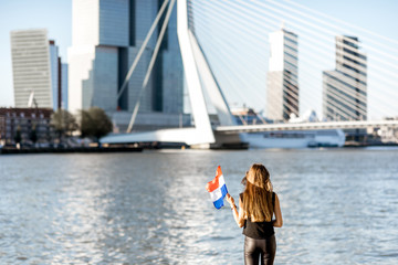 Fototapete - Woman with dutch flag enjoying beautiful cityscape view on the modern riverside during the morning in Rotterdam city