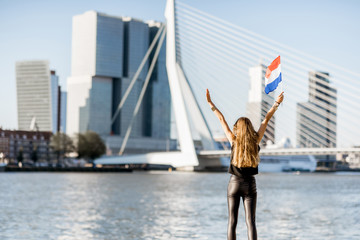 Photo sur Aluminium Rotterdam Woman with dutch flag enjoying beautiful cityscape view on the modern riverside during the morning in Rotterdam city
