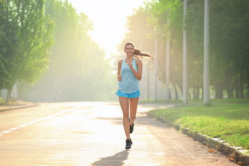 Morning of young sporty woman running outdoors
