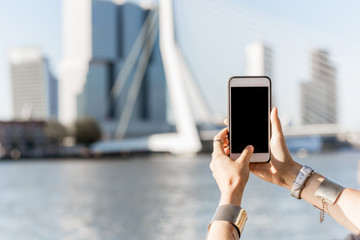 Fototapete - Holding a smartphone with empty screen on the modern cityscape background in Rotterdam city