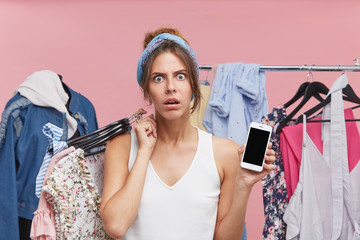 Angry young pretty woman looking with dissatisfaction into camera, keeping hangers with clothes on shoulder, holding smart phone in hand with blank screen for your advertisment or promotional text