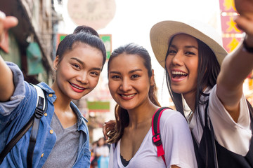 Three asian girlfriends taking selfies in Chinatown, Bangkok