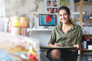 Smiling female artist wearing casual clothes sitting in her cabinet with sketches and colorful paint, having happy expression while being glad to create beautiful picture. Painter working in workshop