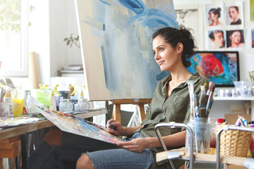 Thoughtful dreamy young European female artist bringing her creativity to life, sitting in her modern workshop interior with palette and painting knife. Hobby, job, occupation, art and craft concept