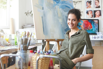 Professional female painter sitting at chair in art studio, keeping hands in pockets of her shirt, smiling gently while resting after drawing picture with watercolors. People, hobby, painting concept