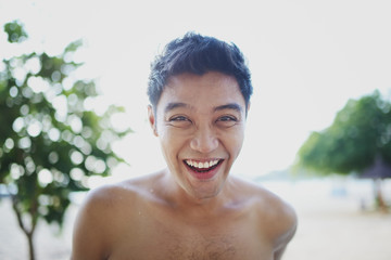 Young man laughing on a beach