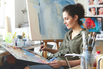 Portrait of beautiful female artist in casual clothes, mixing brightful colors, drawing on easel while sitting in art studio. Brunette female painter at work. Creativity, art, painting concept