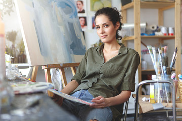 Trendy-looking positive talented young Caucasian woman artist relaxing on chair next to easel in workshop after she finished her painting. Profession, creative, modern art, job and occupation