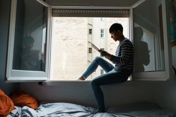 Man sitting in window with digital tablet