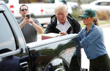 U.S. President Donald Trump and first lady Melania Trump help volunteers hand out supplies to residents at a relief supply drive-thru during a visit with flood survivors and volunteers in the aftermath of Hurricane Harvey in Houston