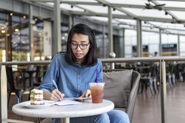 Young Woman Jotting Down Some Information At A Cafe