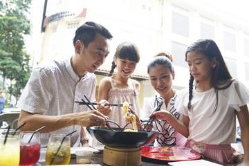 Happy family of four celebrating Chinese New year with Yu Sheng