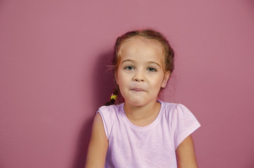 Portrait of adorable little girl on pink wall background