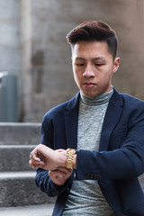 Casual young chinese man checking the time in the street