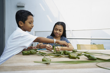 Happy siblings preparing Ketupats for Hari Raya