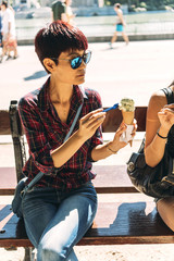 Asian woman eating ice cream on a hot sunny day