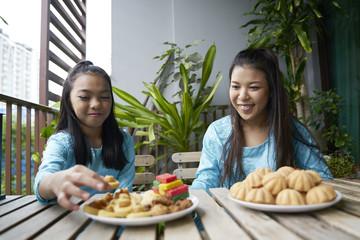 Siblings sharing cookies over Hari Raya