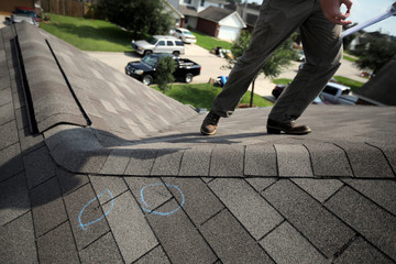 A home insurance inspector conducts an assessment of damages on the roof of a house after tropical storm Harvey in Houston, Texas