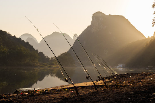 Fishing rods against river at sunset. Idyllic Li River scenery, landscape of Yangshuo in Guilin, China