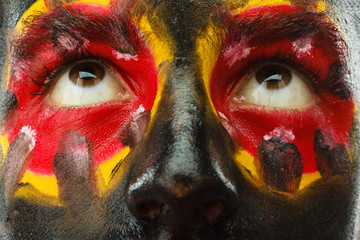 Eyes of Germany sports fan patriot. Painted country flag on man face.
