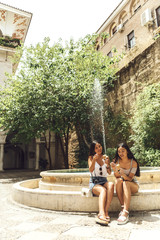 Two Chinese female tourists sitting at font