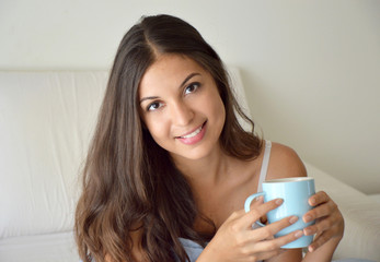 Portrait pretty girl drinking coffee or tea on bed in the morning in apartment