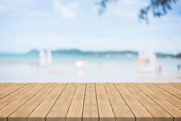 Empty wooden table in front with blurred background at the beach and sailboat,space for montage you products