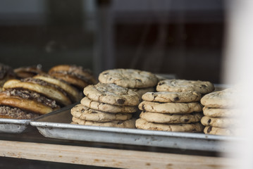 A tray of chocolate chip cookies is seen in the window of a bakery.