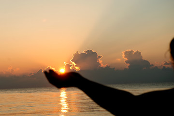 Silhouette human open empty hands with palms up over sun on sunrise background