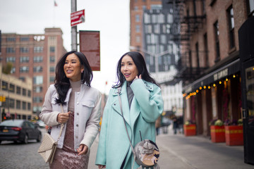 Two girlfriends are walking on the street in meat packing district, New York