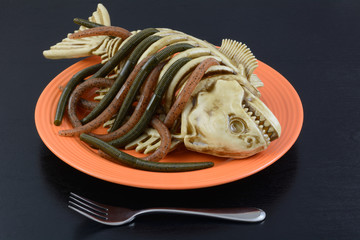 Halloween dinner dish worms crawling out of fish skeleton on orange plate with fork on black table