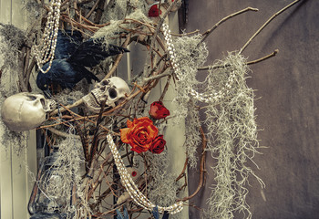 Halloween decorations. black crow, scallop, red rose, cobweb and white worms on a branch of a tree against a wall. Copy space for your text
