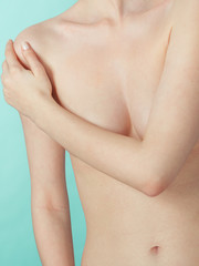 Bare woman covering her breast with hands