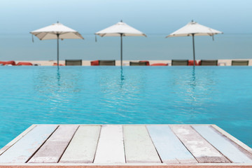 Wood table top and blurred swimming pool with sea background. - can used for display or montage your products.