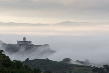 Beautiful view of St.Francis church in Assisi (Umbria, Italy), over a sea of fog at dawn, with hills and trees in the foreground