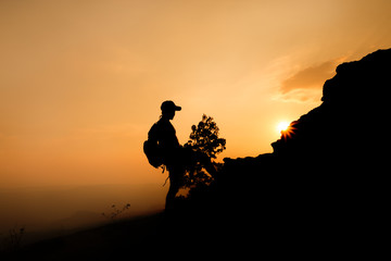 silhouette of a man hiker on the top of the hill