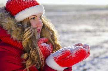 girl holds snow in red gloves