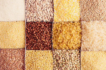 Assortment groats as decorative background. Wheat pearl, bulgur, millet, rice, couscous, semolina, corn grits, buckwheat, quinoa. Top view, closeup.
