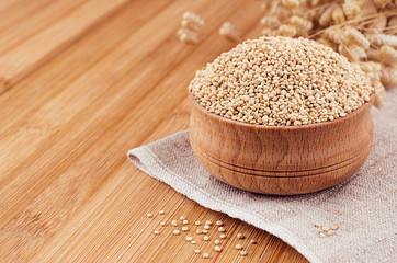Quinoa in wooden bowl on brown bamboo board, close up. Rustic style, healthy dietary groats  background.