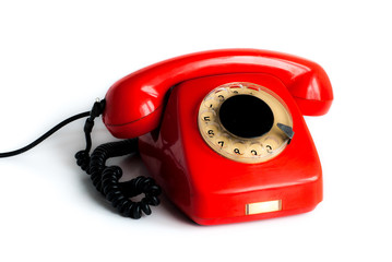 An old red phone against a white background