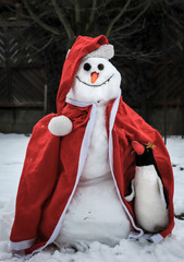 A funny snowman wearing christmas clothes and a penguin