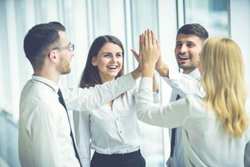 The four business people greeting with a high five