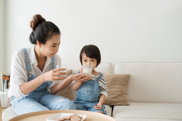 Adorable girl eating cookies and drinking milk with her mother.