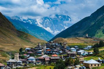 Village Ushguli landscape with massive rocky mountains Bezengi wall, Shkhara on the background in Svaneti, Georgia