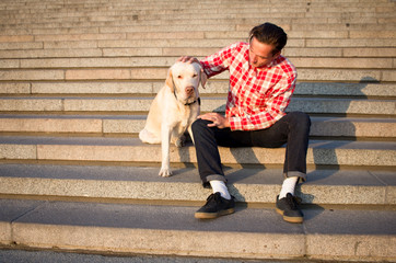 Morning walk of young male and gold labrador dog on the big city stairs at morning