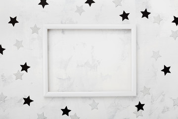 White picture frame with black and silver stars around for fashion blogging mockup. Top view and flat lay.