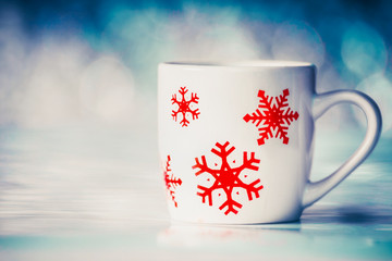 Cup with snowflakes on winter bokeh background, front view